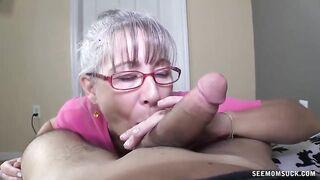 Eine grauhaarige alte Frau mit Brille lutscht einen Schwanz eines jungen Freundes ihres Mannes