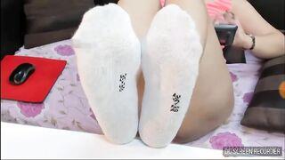 Das Mädchen zeigt auf der Webcam Beine in weißen Socken mit Zahlen an der Ferse.