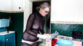 Reife Frau ohne Höschen in der Küche, die das Abendessen vorbereitet