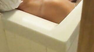 Enkel verdeckt gefilmt, als eine nackte Großmutter durch eine Lücke in der Tür badet