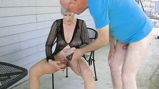 Die grauhaarige Großmutter sitzt auf einem Stuhl und pisst vor dem Großvater in ein Glas