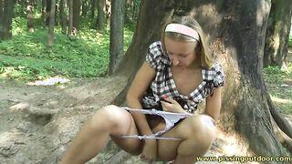 Russische Blondine zog ihr weißes Höschen herunter und sitzt pissend im Park
