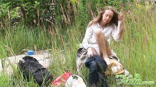 Ein Mann mit einer versteckten Kamera, der als Mädchen gefilmt wurde, zieht sich im Gebüsch um