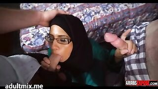 Junges muslimisches Mädchen in Gläsern saugt zwei Schwänze gleichzeitig