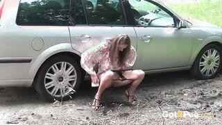 Junge Frau pisst in der Nähe des Autos auf dem Weg zur Hütte