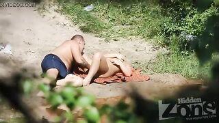 Voyeur fotografiert mit einer versteckten Kamera, während ein russisches Paar an einem Fluss fickt
