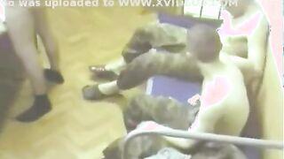 Soldaten drängen eine Frau in einer Kaserne