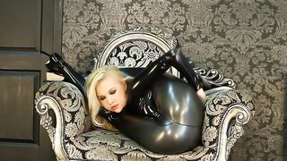 Turnerin in einem schwarzen Latexanzug posiert bei einem Fotoshooting und wirft ihre Beine hinter den Kopf