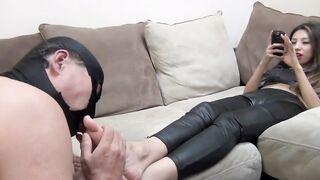 Sklave leckt die Beine und Schuhe einer reichen Dame in Latexgamaschen für Geld