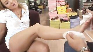 Der Verkäufer poliert die Pediküre und die Füße einer leidenschaftlichen Blondine