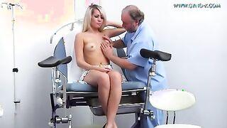 Ein älterer Arzt untersucht ein Mädchen auf einem gynäkologischen Stuhl