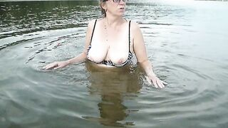50 Jahre alte dicke Frau mit Brille badet in einem Teich und zeigt Titten
