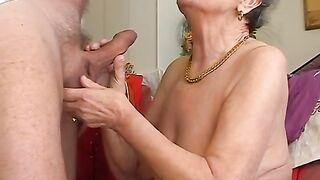 Die faltige grauhaarige alte Frau schluckt tief einen Schwanz