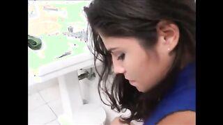 Ein Mädchen sitzt auf der Toilette und rasiert sich gründlich, und ein Freund nimmt sie ab